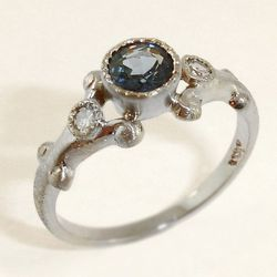 """Round bezel set blue sapphire with two smaller diamonds in 14kt white gold setting, $2,100 at <a href=""""http://www.ellevennyc.com/engagement/""""><b>Elleven</b></a>"""