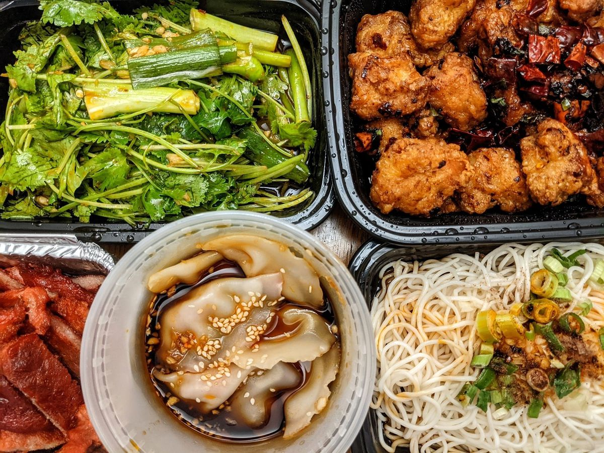 Overhead view of five open takeout containers of Sichuan food, including a cilantro and green pepper salad, dry fried chicken, wontons, noodles, and more.