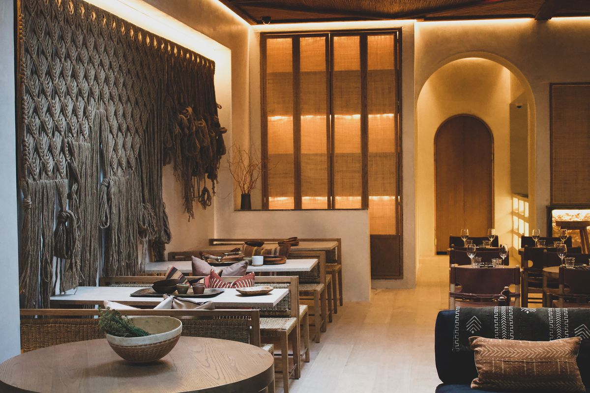 A sleek interior of a restaurant with sandy walls and cool yellow tones.