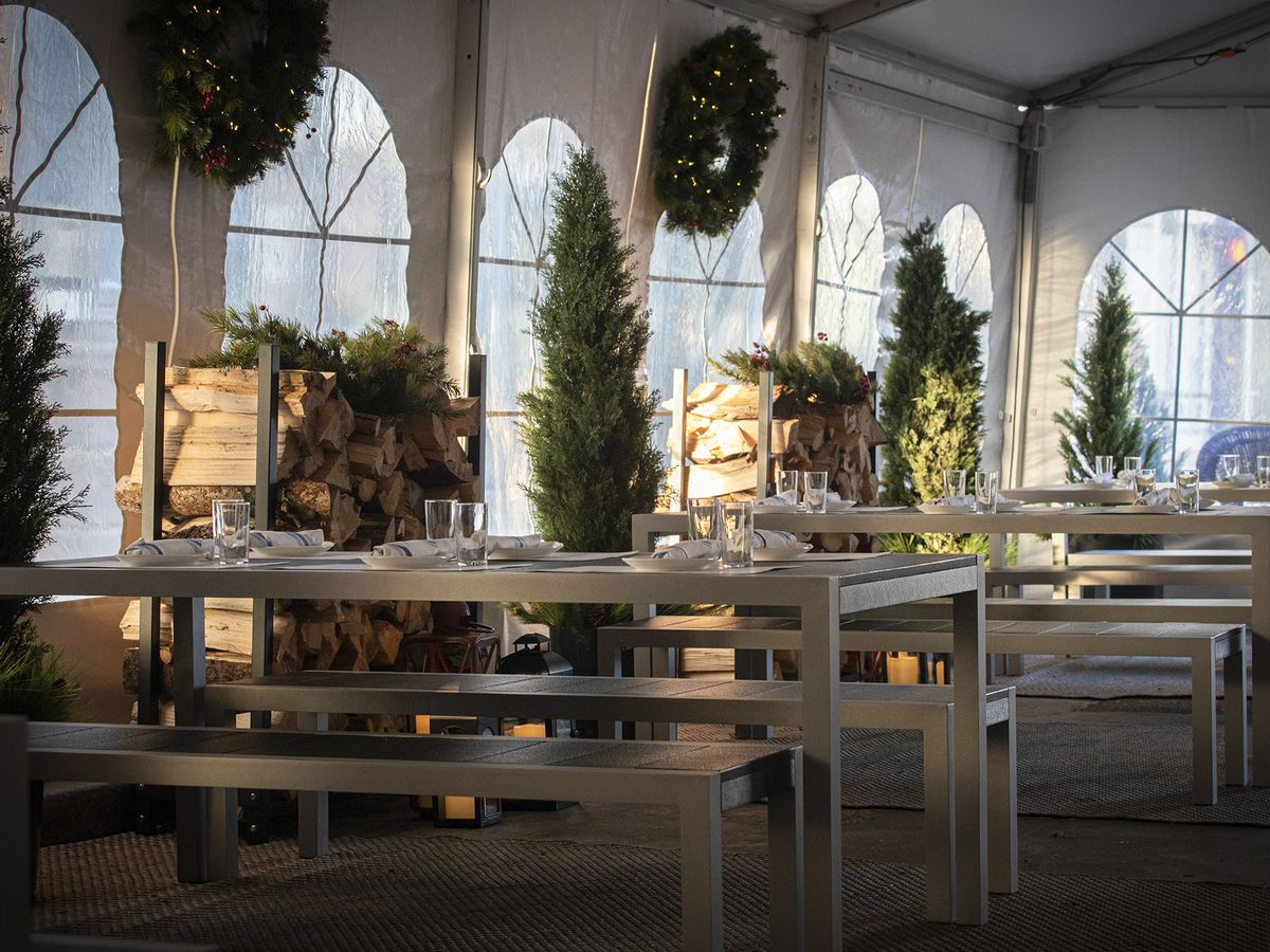 A tall tent with steel tables and benches, stacks of wood, small trees and wreaths