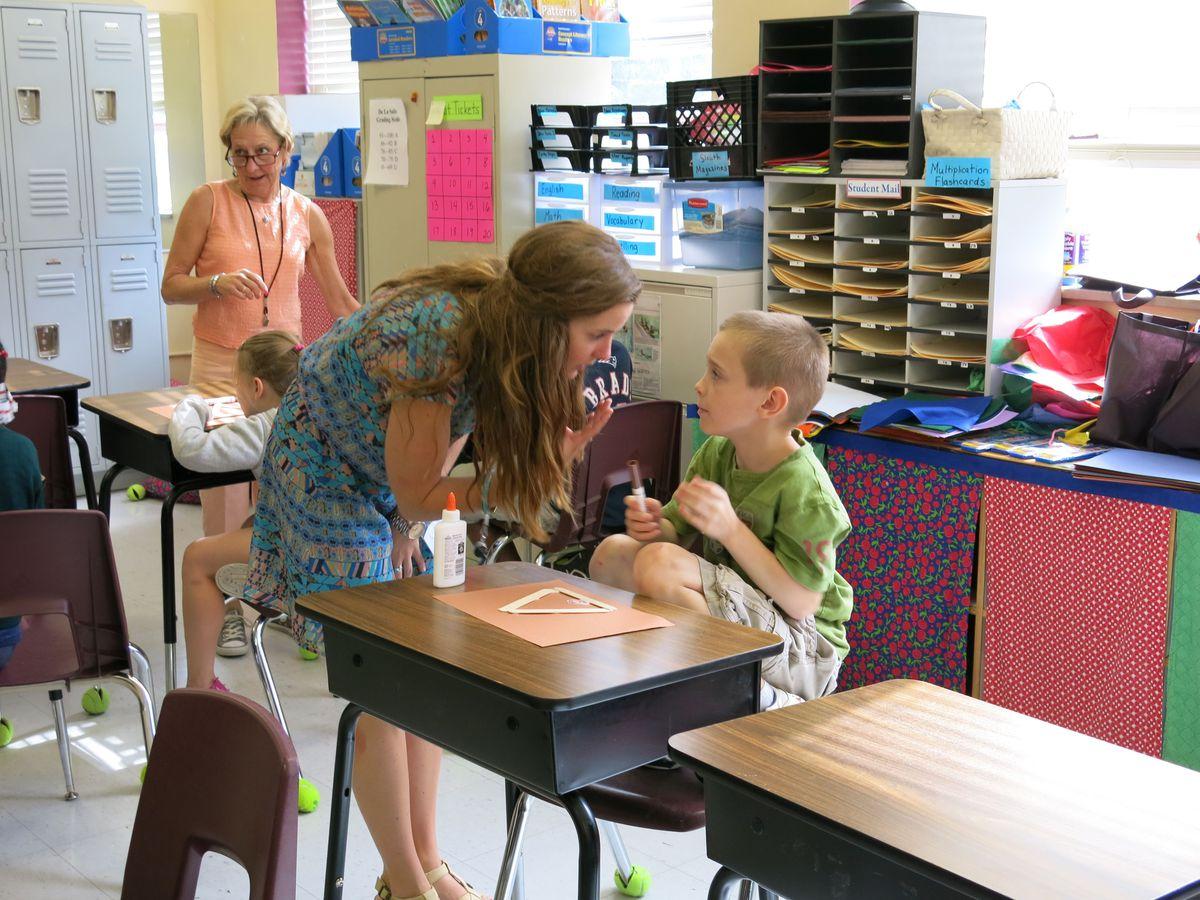 Erika Hansen helps a third grade student work on a craft at a reading program at De La Salle Elementary.