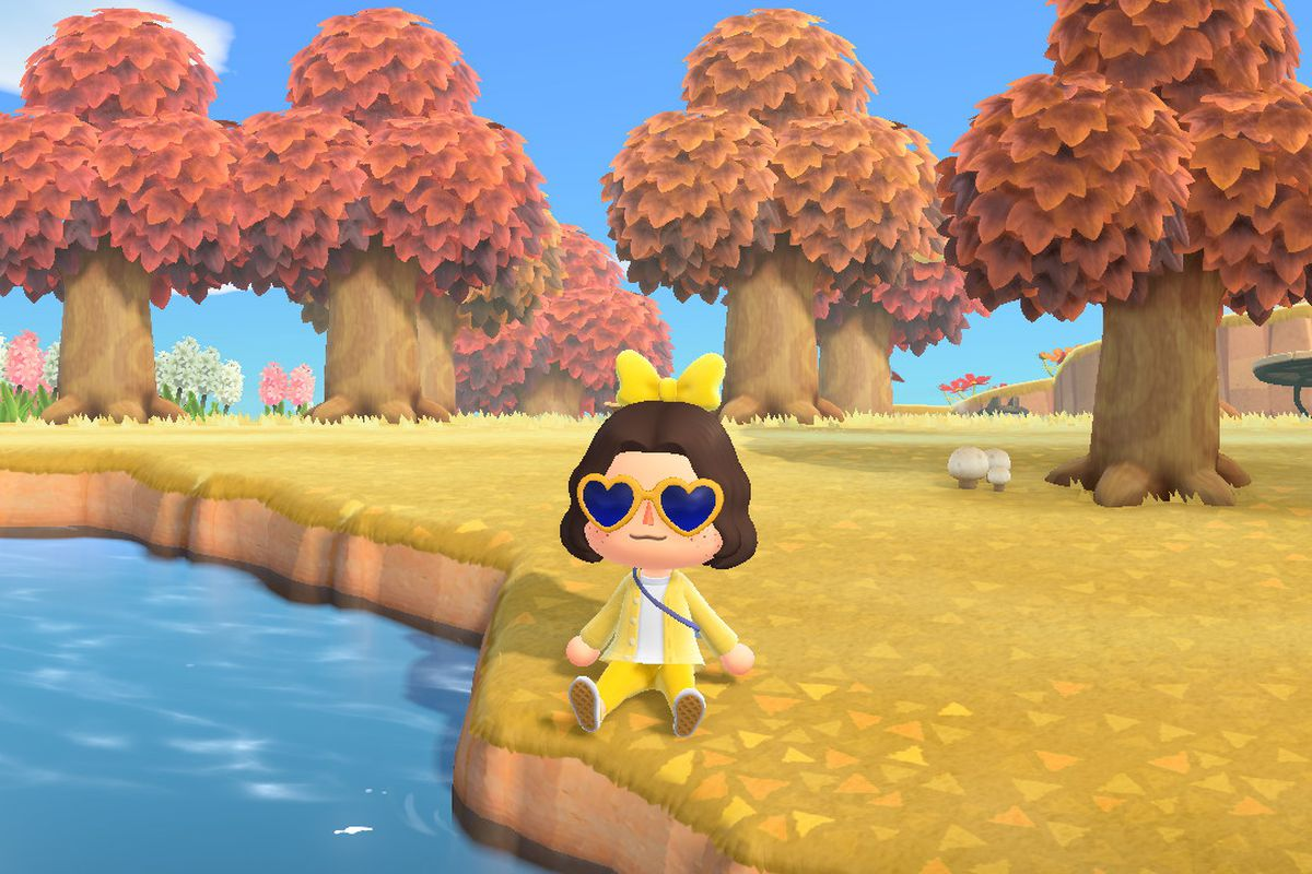 Animal Crossing character wearing an all yellow outfit sitting along by a river