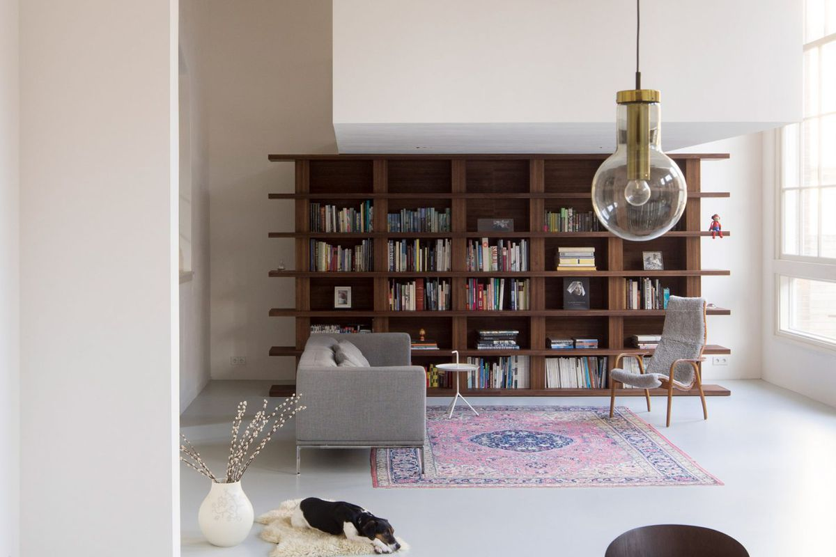 Shot of minimalist lounge area with large wooden bookshelf in white, airy room.