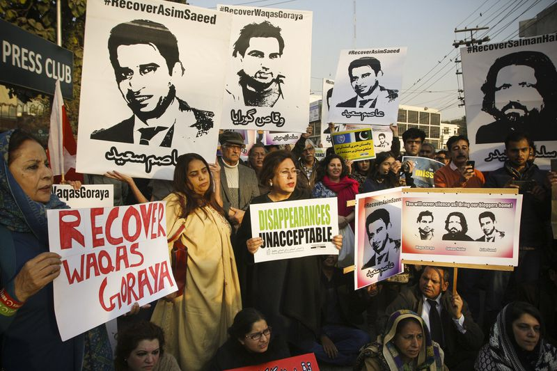 Protesters hold images of three bloggers who disappeared during a rally in Lahore on January 12, 2017.