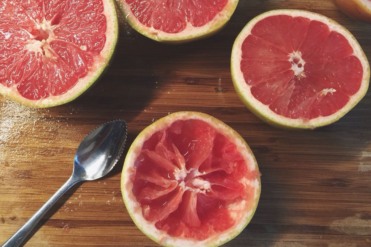 A grapefruit spoon sits on a wooden surface surrounded by halved grapefruits.