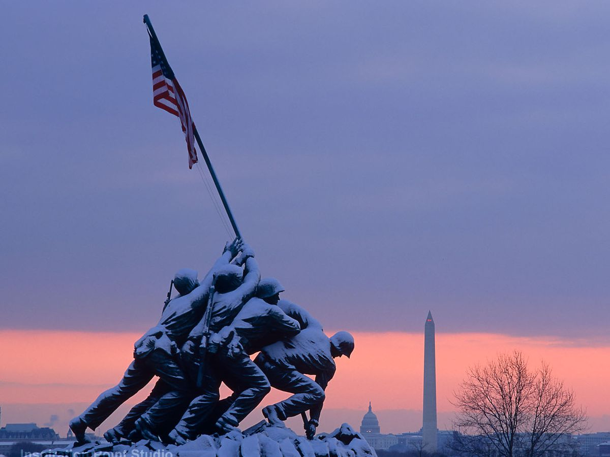 The U.S. Marine Corps War Memorial in the winter with snow covering the monument. The monument depicts the soldiers of Iwo Jimo carrying a United States flag.