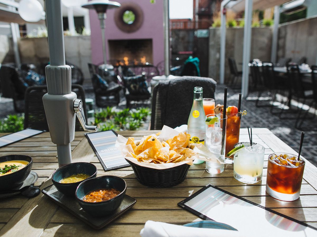 A table set with chips, various dips, and cocktails, with a courtyard and outdoor oven visible in the background