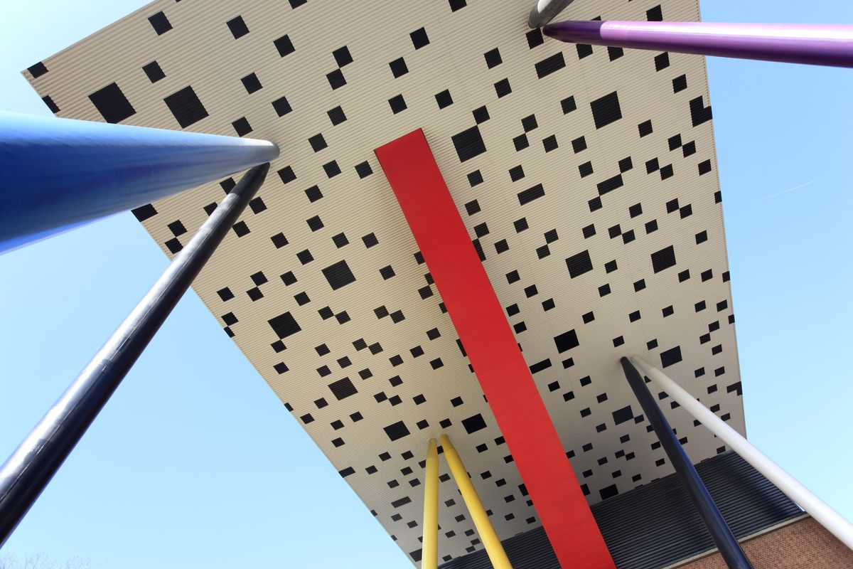 View of the underside of a checkerboard-patterned building with stilts in different colors supporting it.