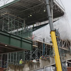 Concrete panels at the end of the first base line grandstands have holes drilled, toward the top of each panel