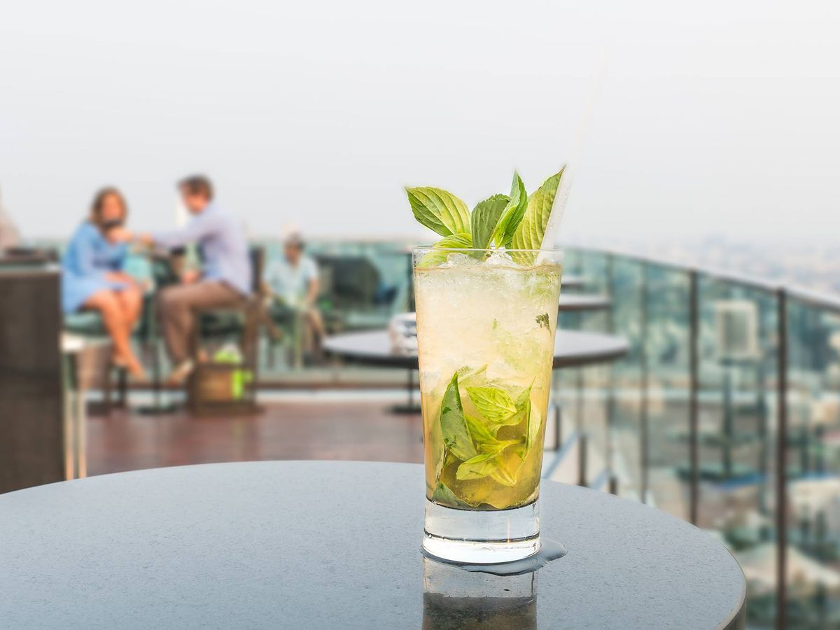 A cocktail garnished with mint sits atop a table on the rooftop of Seattle's Charter Hotel.