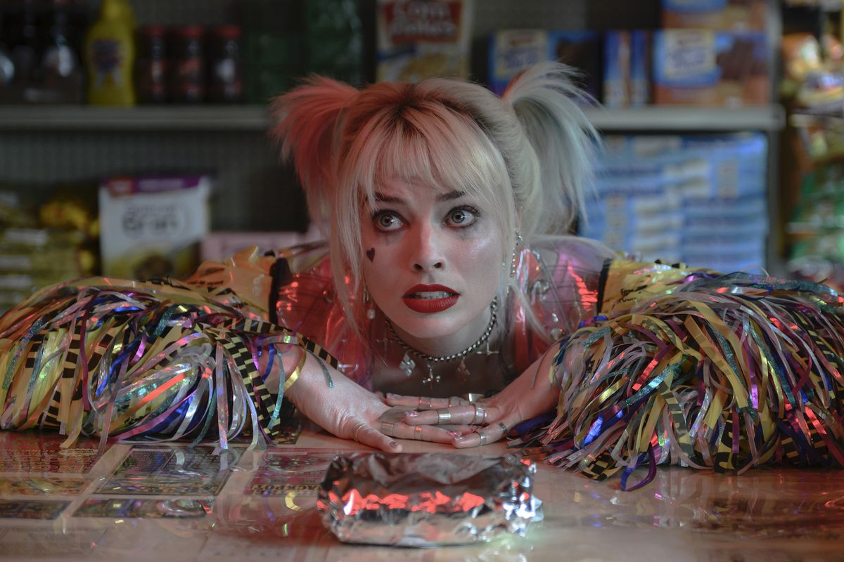 Margot Robbie rests her arms on a deli counter and looks pleadingly at her breakfast sandwich as Harley Quinn in Birds of Prey.
