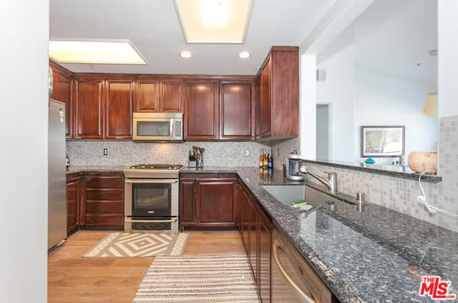 A long kitchen with medium-stained cabinets, stainless steel appliances, and speckled gray and white marble countertops.