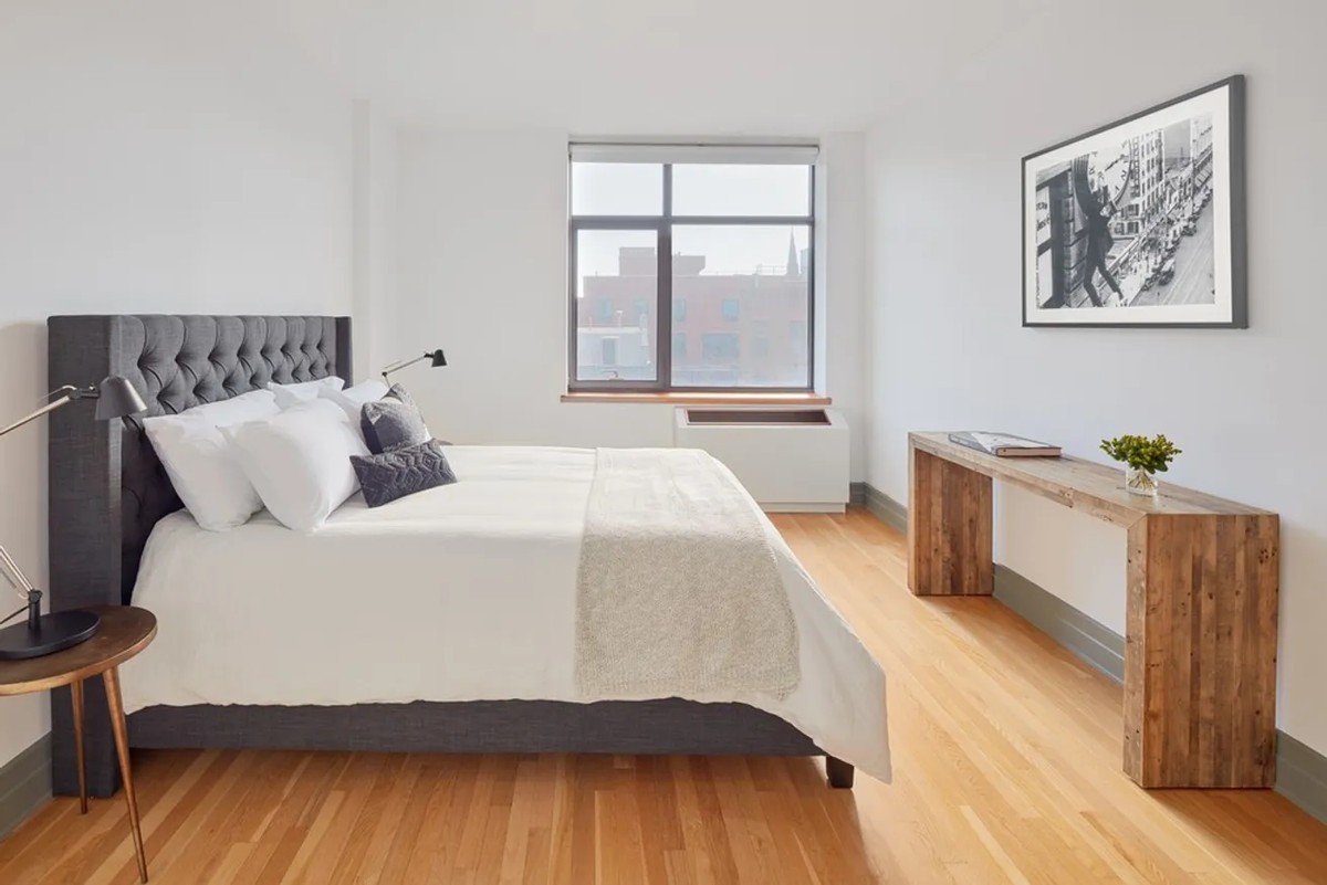 A bedroom with a large bed, a window, and hardwood floors.