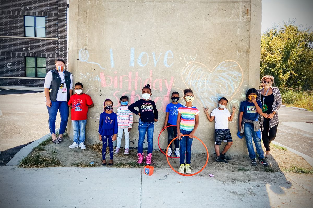 """Children and two adults, wearing masks, stand against a wall with the words, """"I love birthday school,"""" written in chalk."""