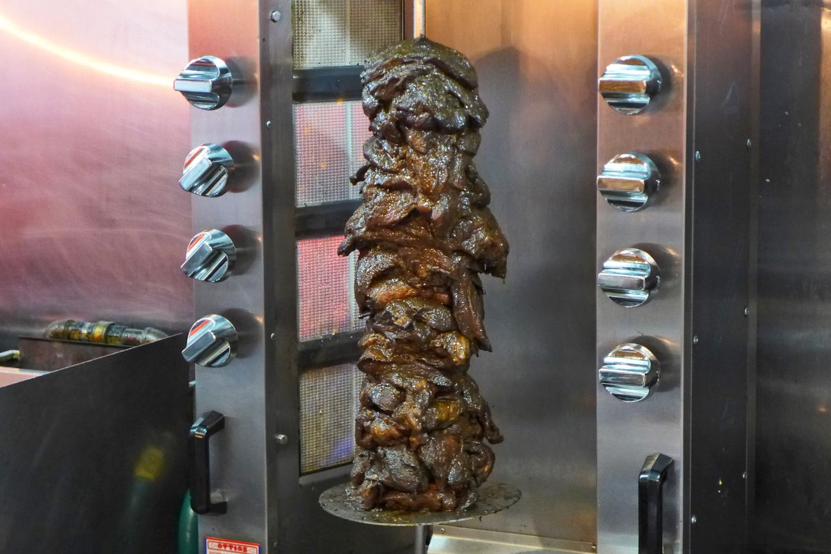 A vertical spit is threaded through a pile of jerk pork pieces, which are very dark.