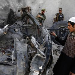 An Afghan man examines the remains of a car after three suicide bombers were killed before they reached Jalalabad airport, which security forces say was their target, in Jalalabad, east of Kabul, Afghanistan on Sunday, April 15, 15 2012. The Taliban launched a series of coordinated attacks on at least seven sites across the Afghan capital on Sunday, targeting NATO headquarters, the parliament and diplomatic residences. Militants also launched near-simultaneous assaults in three other eastern cities. (AP Phot/Rahmat Gul)
