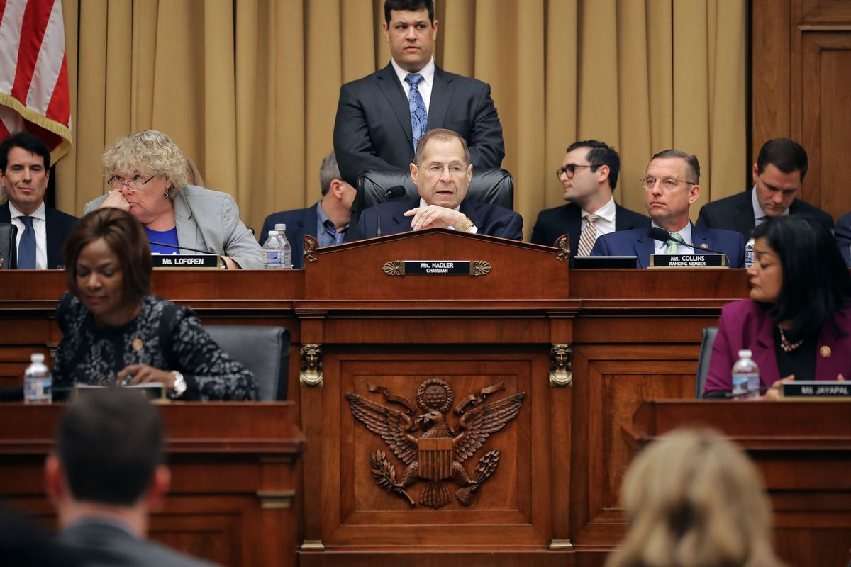 Nadler sits behind a bench featuring the seal of the United States surrounded by members of the Judiciary Committee.