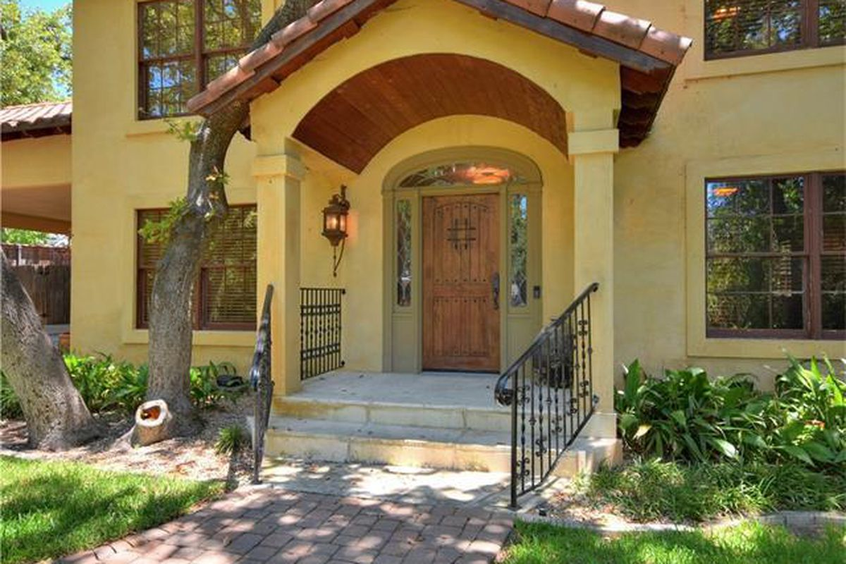 Front door of two story yellow stucco house