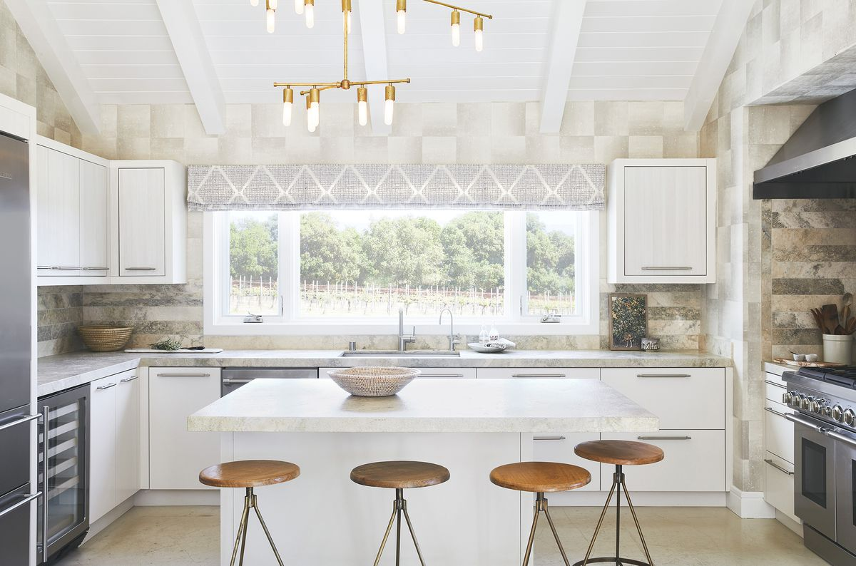 Two bold patterned wallpapers (a plaid an a toile showing a hunting print) decorate the dining room. In the kitchen, a softer textured wallpaper energizes the kitchen.