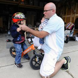 Kelly Burton helps 3-year-old Logan put his helmet on while holding 2-month-old Raiger in his arms as they go outside to play Sept. 25.