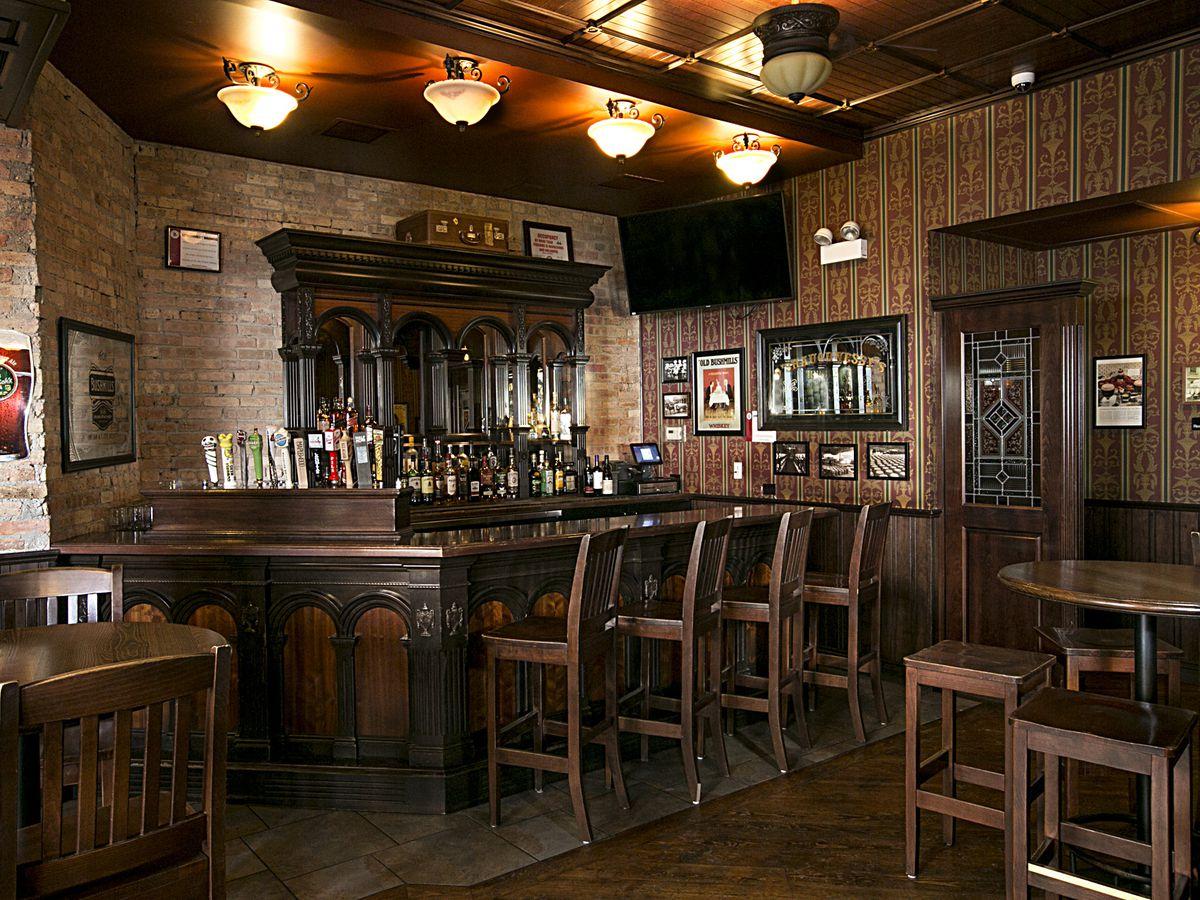 A dark wood bar with four stools.