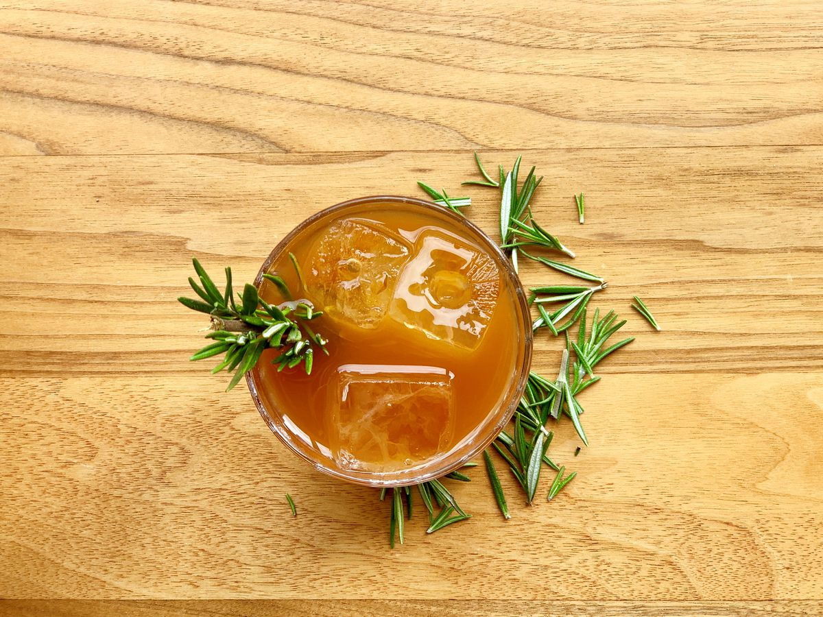 An orange cocktail in a glass with rosemary.