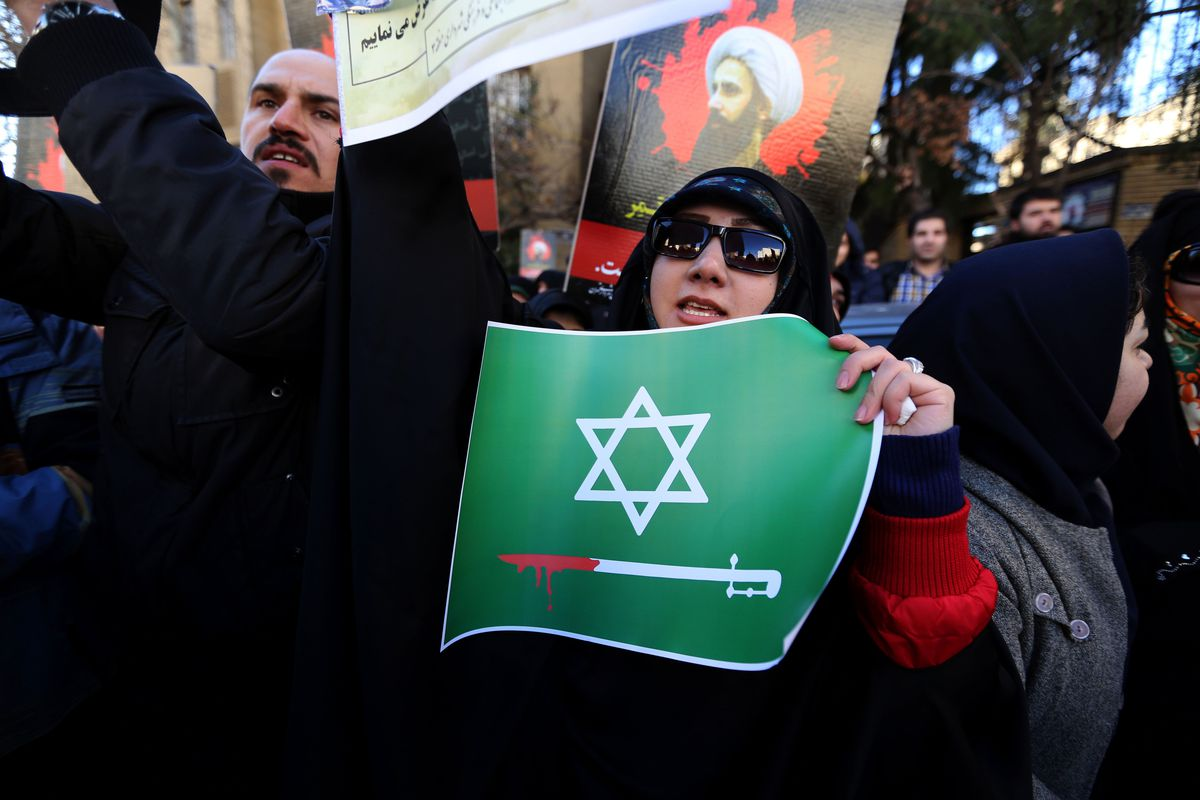 An Iranian woman holds an anti-Saudi placard at a protest outside the Saudi embassy in Tehran. Behind her is a photo of Shia cleric Nimr al-Nimr, whom Saudi Arabia executed.