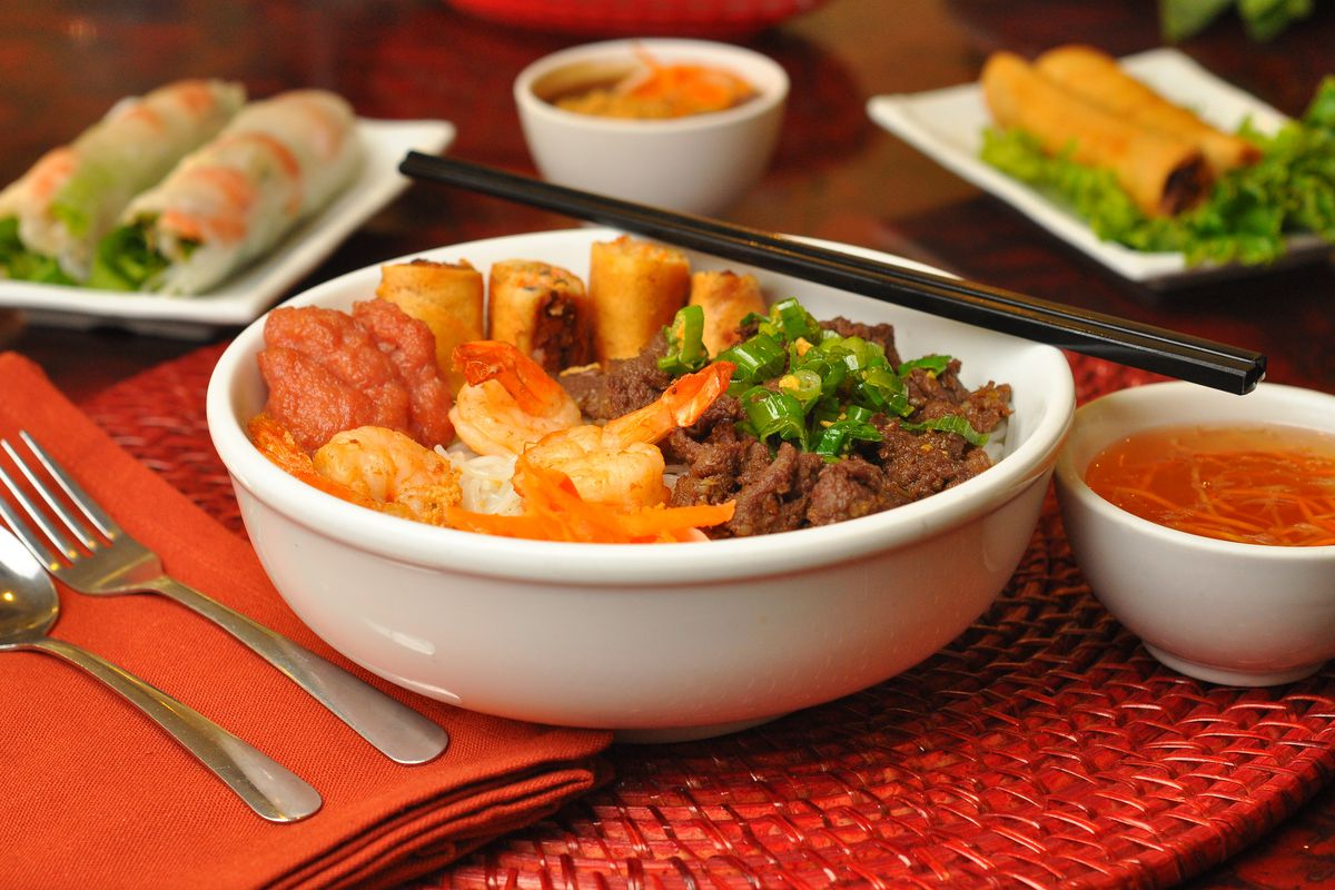 A table with Vietnamese dishes on it.