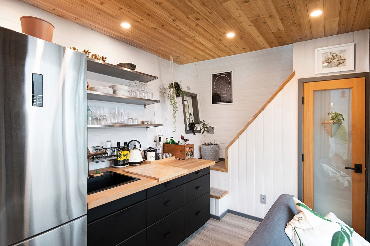The kitchen has wooden counters, black cabinetry, and a stainless steel fridge. In the corner, stairs lead to a lofted bedroom.