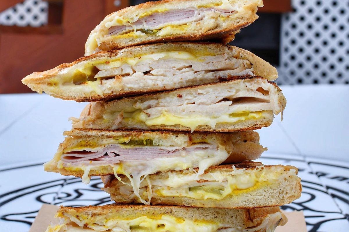 A stack of Cuban sandwiches on the counter of Cubanos ATL in Sandy springs, GA