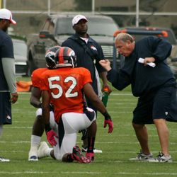Broncos LB Wesley Woodyard listens to his coach during linebacker hand drills