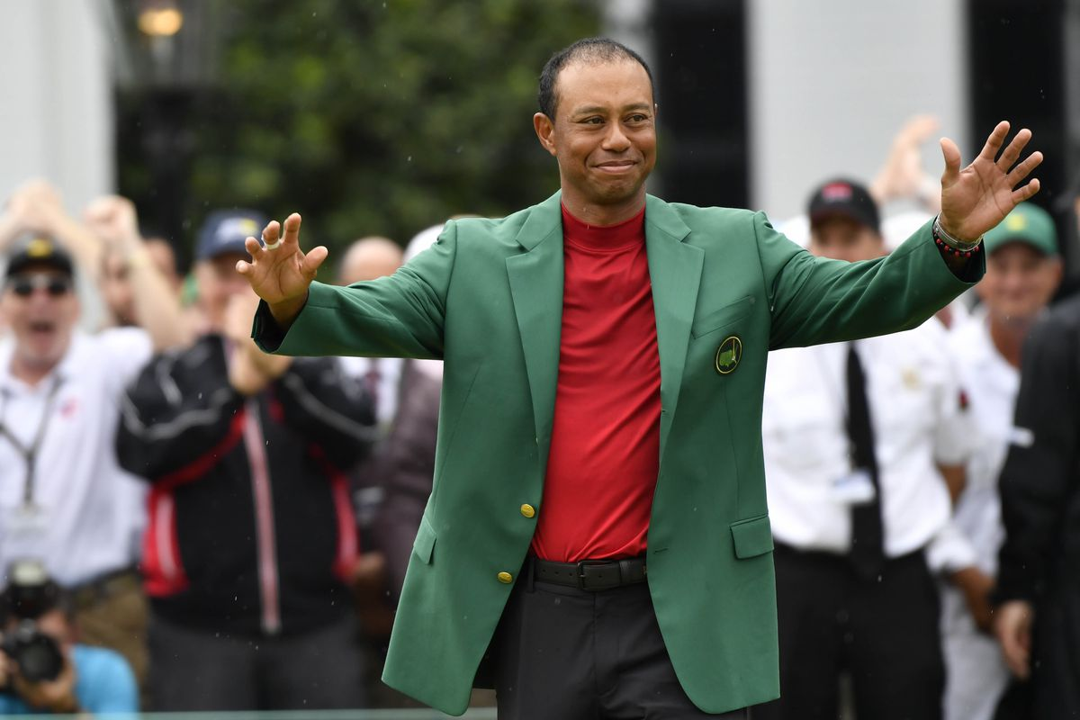 Tiger Woods celebrates with the green jacket after winning The Masters golf tournament at Augusta National Golf Club.