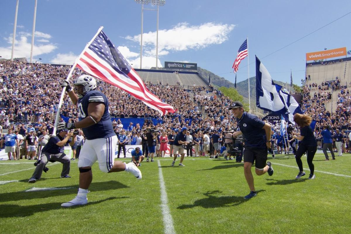 Mo Langi carries the flag into LaVell Edwards Stadium on Saturday, August 26, 2017.