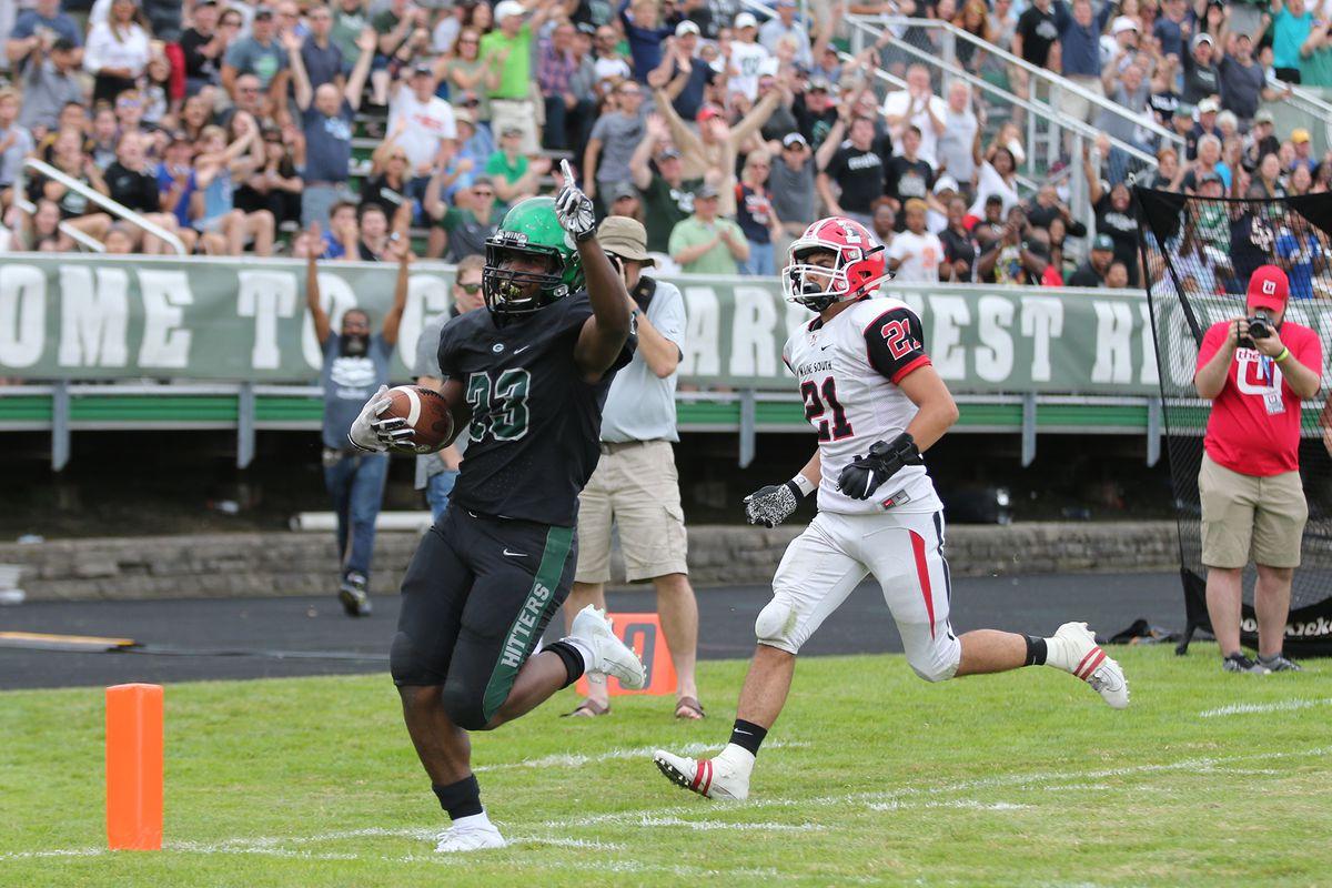 Glenbard West's Jalen Moore (23) raises a finger as he scores one of his touchdowns against Maine South.