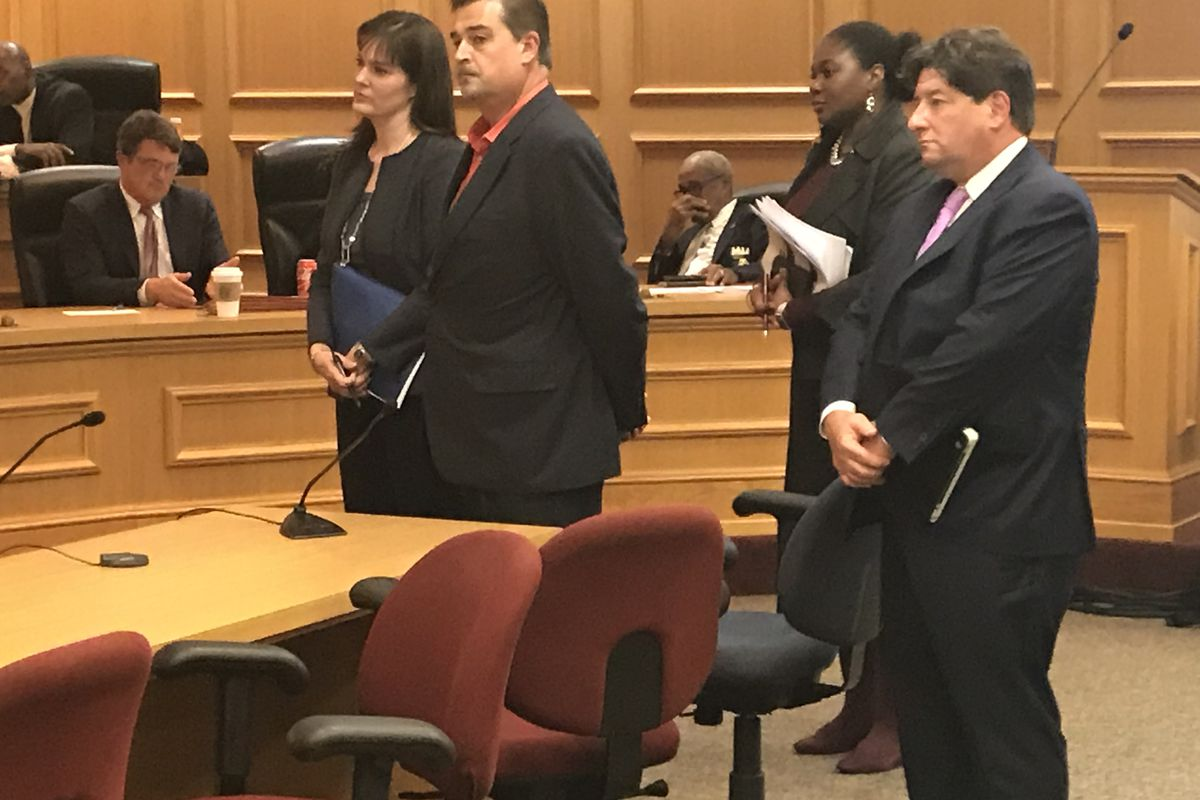 McQueen (far left) pauses with her team, including Questar CEO Stephen Lazer (far right), to hear a few final comments from lawmakers.