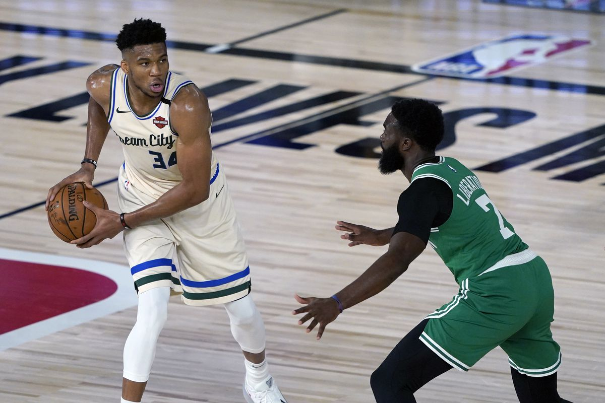 Giannis Antetokounmpo of the Milwaukee Bucks looks to pass around Jaylen Brown of the Boston Celtics during the first half of an NBA basketball game Friday, July 31, 2020, in Lake Buena Vista, Florida.
