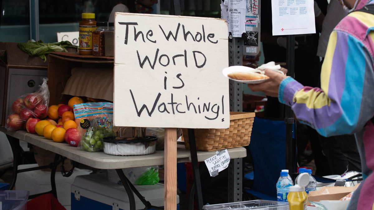 """A hand holds up a plate of food right next to a sign that says """"The Whole World Is Watching!"""""""