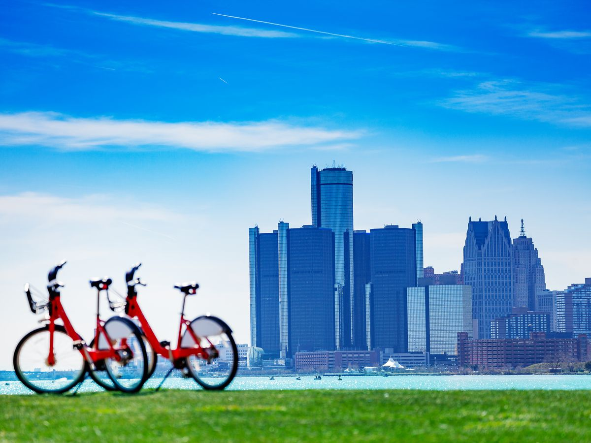 Two bicycles are parked on a grassy patch with the skyline of Detroit in the background