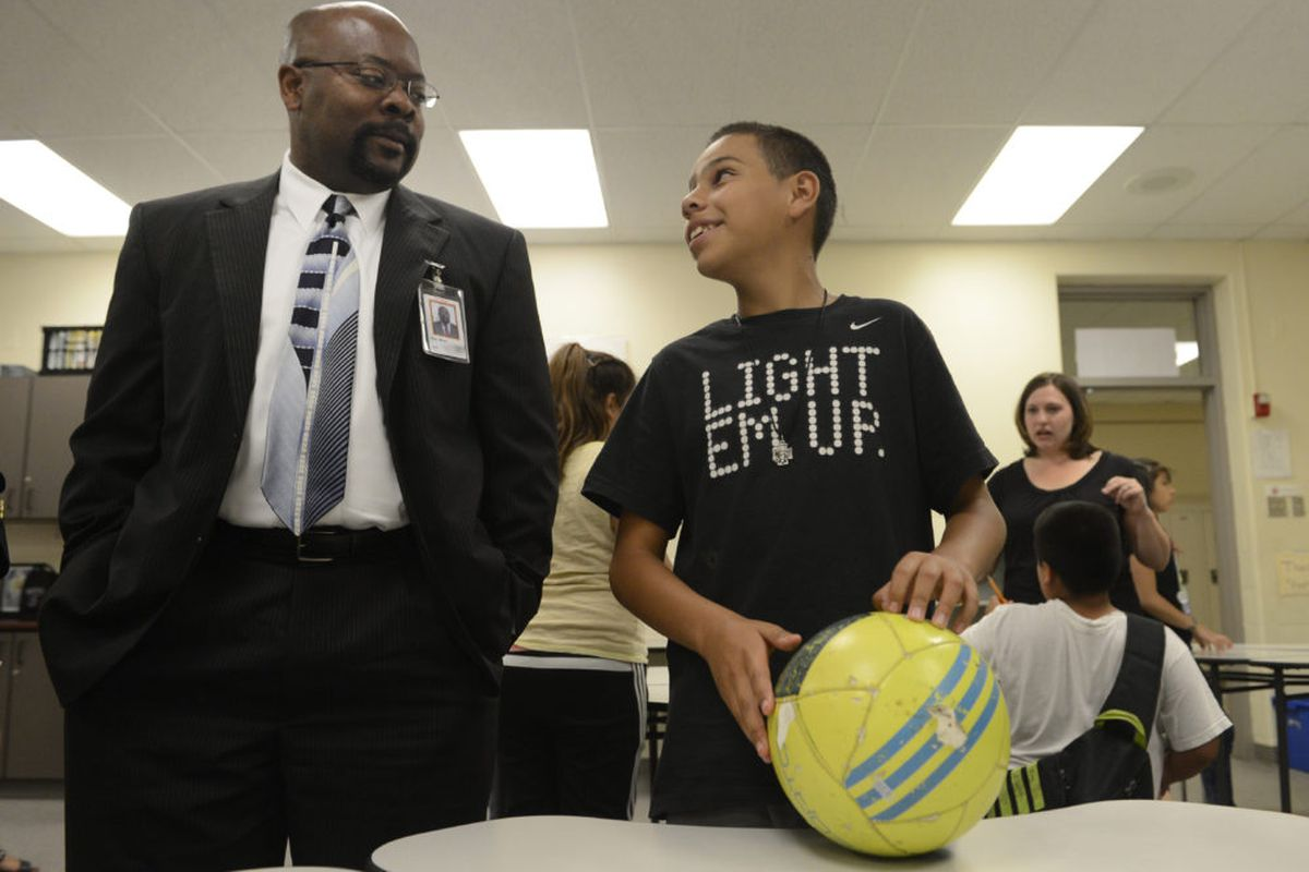Aurora Public Schools Superintendent, Rico Munn, left, talks with a student about World Cup soccer at North Middle School in 2014.