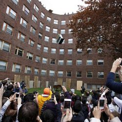 RETRANSMISSION TO CORRECT DAY OF WEEK - A crowd watches as a piano falls from the roof of Baker House dormitory at Massachusetts Institute of Technology in Cambridge, Mass., Thursday, April 26, 2012. The annual event which began in 1972 is staged to celebrate the last day students can drop classes without having them appear on their college transcript.