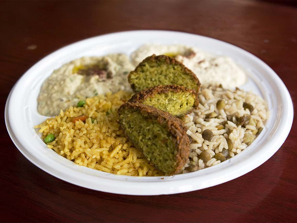 A plate of falafel, rice, and hummus.