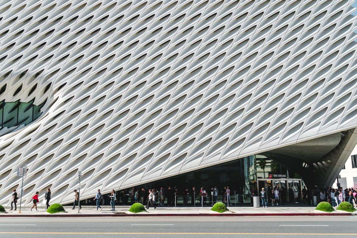 People wait in line while standing in front of a large white contemporary building with holes cut into it in a diagonal pattern.
