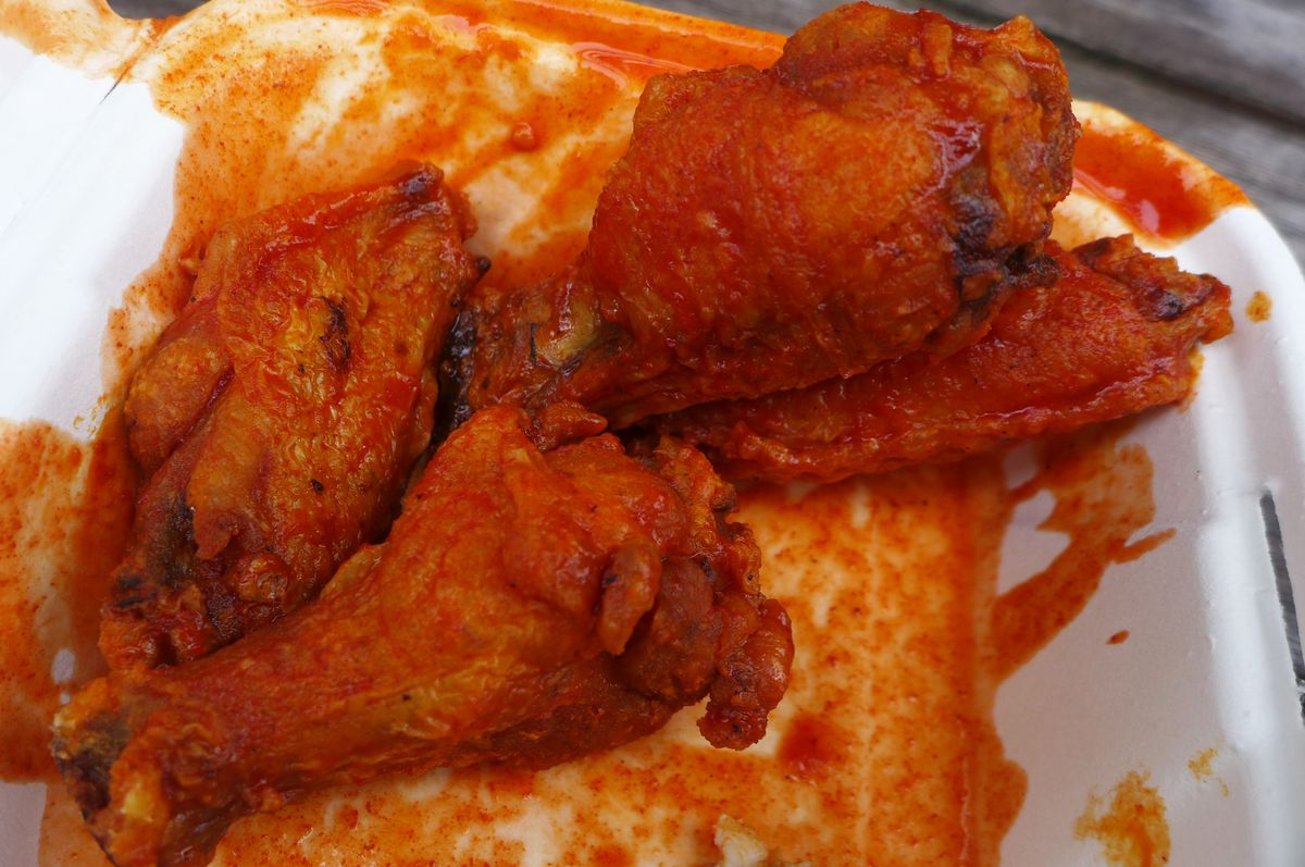 A tight shot of four very bright red and glistening chicken wings.