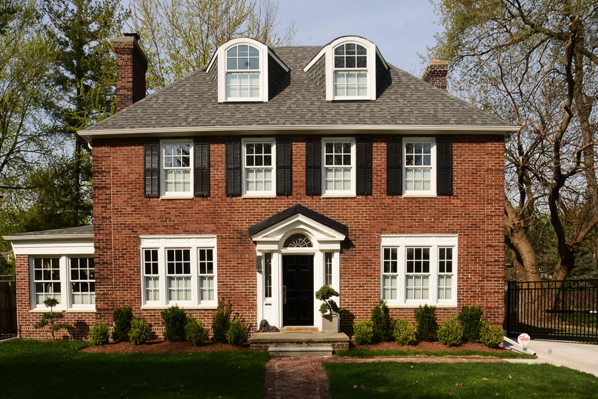 Two story brick colonial with black window shutters on second floor and two dormer windows.