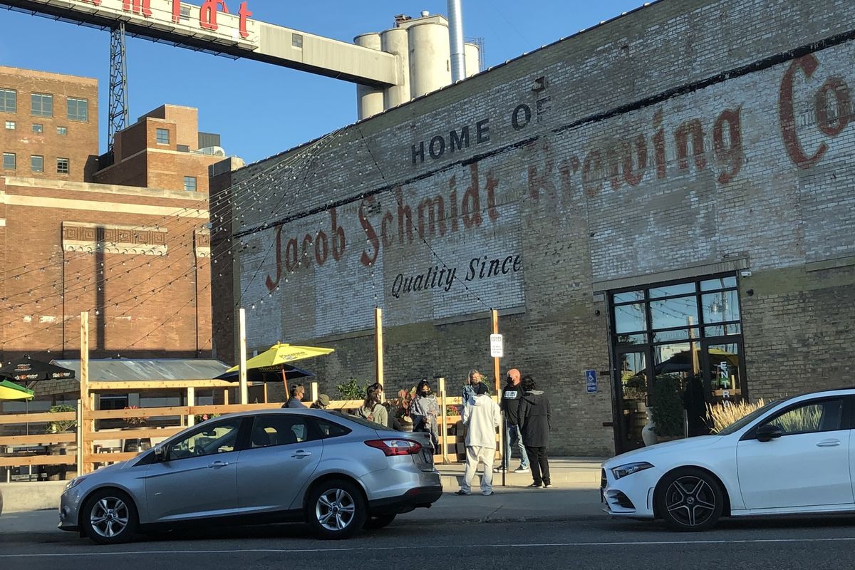 The historic Schmidt Brewery is a gathering of people, backs turned to the street. In front of them, Brian and Sarah Ingram, stand with masks, actively listening