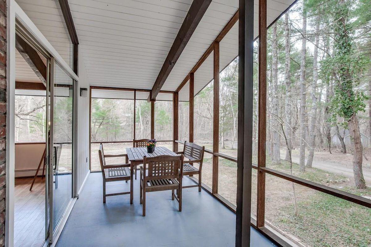 A long, airy, rectangular sunroom off a house.