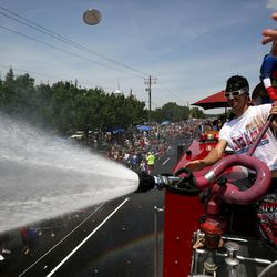 Greg Williams sprays the crowd with water during the Fourth of July parade in Kaysville on Saturday, July 4, 2015.
