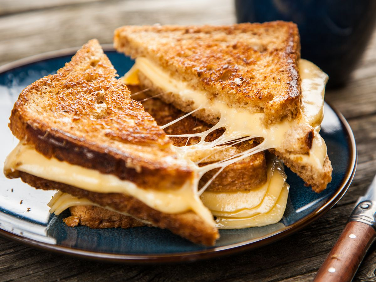 A plate with two grilled cheese sandwiches stacked on top of each other
