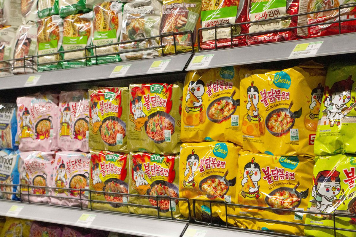 A closeup of colorful Asian snack packages on an H Mart shelf.