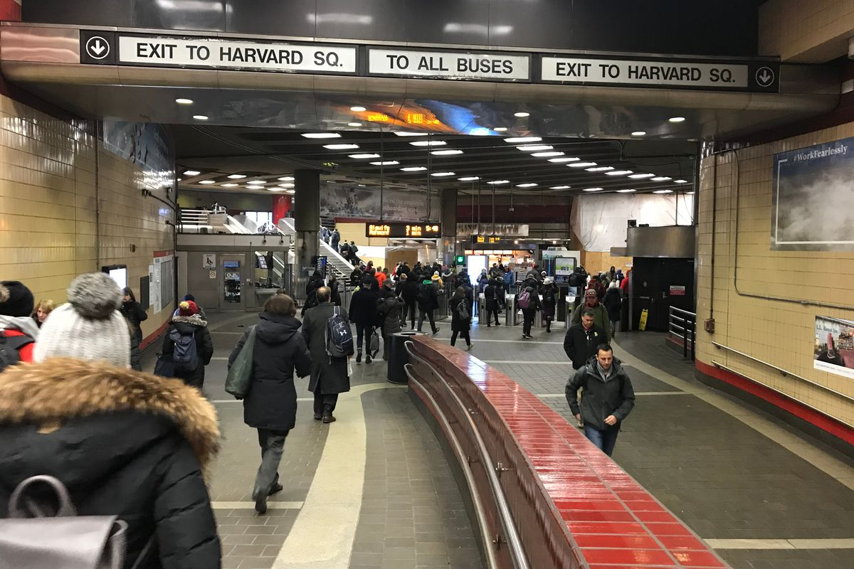 A busy subway station with people walking in different directions toward outgoing and incoming train lines.
